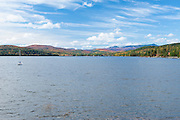 Schroon Lake<br /> Adirondacks, NY<br /> Under a mixed sky, Schroon Lake was pretty agitated with chop.  I had climbed Pharoah Mountain, then took the back road to end up here in the little township of Adirondack, where sky and color pulled me and tripod out of the car.   How often do the elements come together for a perfect day on the water with a sailing breeze and this panorama?  You can't pick your days, but I stand and watch the cat boat strain at it's moorings as if it knows this is the one.  It is ready to tack to the north end, closer to the crazy autumn quilt of Mount Severance and the Hoffman Wilderness.  Once there, it could be all out for a run south east down the lake with the push of the breeze, before pulling up and making the long journey back to this point.  Were I a sailor, it's what I'd do, but that's another missed opportunity.