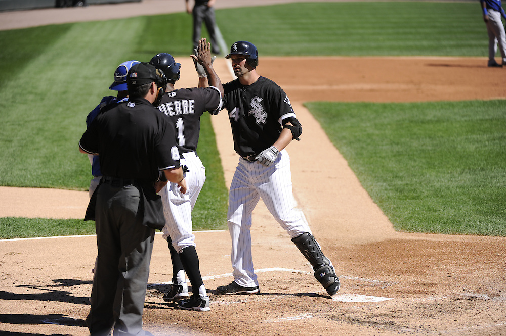 CHICAGO - SEPTEMBER 12:  Paul Konerko #14 is greeted by Juan Pierre #1 of the Chicago White Sox after Konerko hit the first of two, two-run home runs in the first inning against the Kansas City Royals on September 12, 2010 at U.S. Cellular Field in Chicago, Illinois.  The White Sox defeated the Royals 12-6.  (Photo by Ron Vesely)