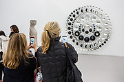 "New York, NY - 5 May 2017. The opening day of the Frieze Art Fair, showcasing modern and contemporary art presented by galleries from around the world, on Randall's Island in New York City. Two women take photos of Olafur Eliasson's ""Your hope diagram,"" an assemblage of partially silvered crystal spheres and stainless steel in the Tanya Bonakdar Gallery."