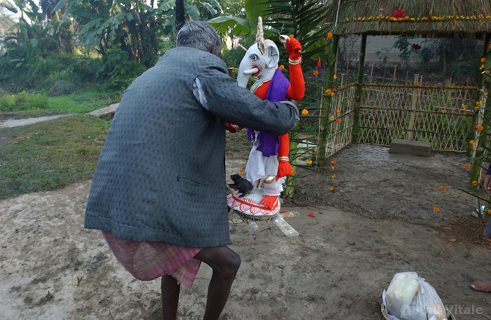 """Villagers, many of whom lost their homes, crops, and even a man who was killed by elephants perform a """"puja"""" or holy ceremony to the Hindu God Lord Ganesha who is half human and half elephant to ask him to protect the village from real elephants coming back and causing more destruction  near Tezpur in Assam, eastern India January 6, 2004.  Villagers have been forced to stay up lighting fires, banging tin cans, throwing firecrackers to keep elephants from destroying their crops, homes and somtimes killing people. India and its sacred elephants are threatened by the deforestation caused by encroachment of the reserved land and natural forests.  As a result, wild elephants are rampaging through villages, killing people and destroying their homes and crops. (Ami Vitale)"""