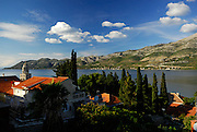 Elevated view over trees and rooftops, looking North-West across the Peljeski Kanal, toward the Peljesac Peninsular (Croatian mainland), with large cloud formation on mountain. Island of Korcula, Croatia