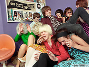 A group of friends wearing retro, vintage clothing, piled on top of each other on a bed, Southend, UK 2006