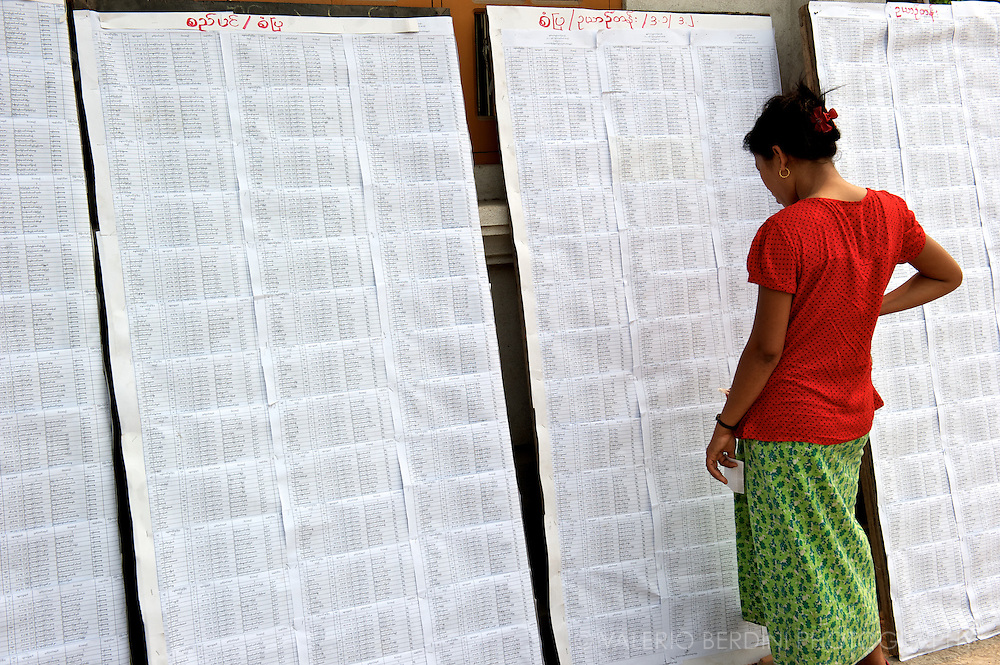 A woman checks the candidates on the long lists exposed at the poll station. Mandalay, Myanmar. 2012