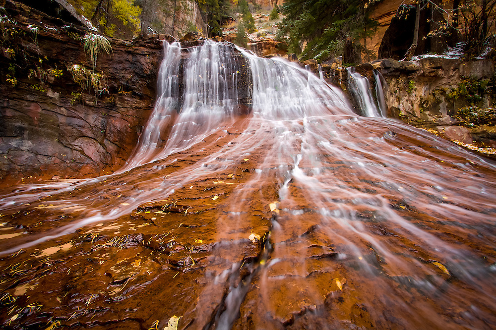 A cascade of water over the orange sandstone on the Left Fork of North Creek in Zion National Park.  The river flows over the hard sandstone stream bed that creates numerous waterfalls and cascades.