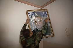 © Licensed to London News Pictures. 04/11/2016. Hamdaniyah, Iraq. Christian militiaman Salam Idris, hangs a picture of his late father, on the wall of his family home in the recently liberated town of Hamdaniyah, Iraq. The picture was taken down and damaged by Islamic State militants when they occupied the house and employed it as a factory for improvised mines.<br /> <br /> Although located close to a front line, littered with improvised explosive devices and pieces of unexploded ordnance the Christian town of Hamdaniyah has only recently been cleared of ISIS extremists who stayed behind to fight. After the town's liberation as part of the Mosul Offensive residents and priests of the town are now free to take short trips to assess damage, salvage possessions and clear up the mess left by militants during their two year occupation.<br /> <br /> Hamdaniyah, and much of the Nineveh plains, were captured by the Islamic State during a large offensive on the 7th of August 2014 that saw the extremists advance to within 20km of the Iraqi Kurdish capital Erbil. Residents of the town, who included many Christian refugees who escaped there after the fall of Mosul, were then forced to seek sanctuary in the Kurdish areas. In the year and two months of the ISIS occupation churches were burnt, homes were put into use as militant accommodation and bomb factories and some buildings destroyed by coalition airstrikes. Photo credit: Matt Cetti-Roberts/LNP
