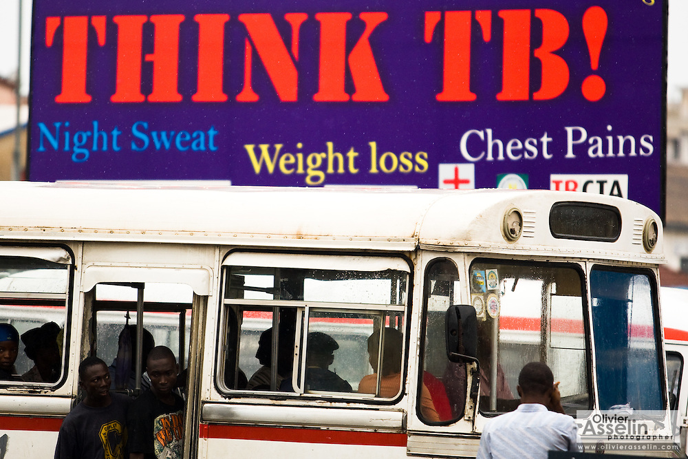 A bus filled with passengers drives by a sign promoting tuberculosis awareness in central Accra, Ghana on Tuesday June 16, 2009.