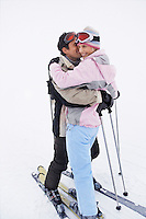Couple embracing standing on skis on ski slope