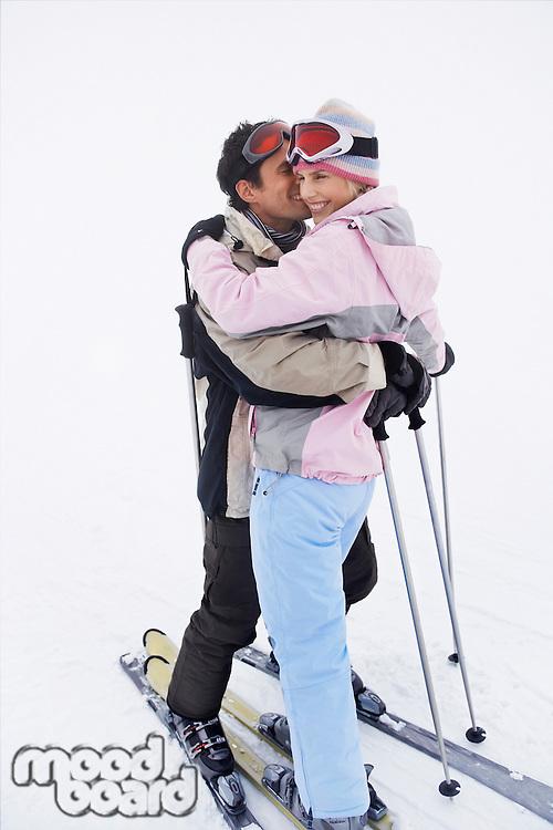 Couple embracing standing on skis on ski slope