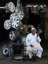 © Licenced to London News Pictures. 26//11/2014. Delhi. India.  <br /> General view of a Muslim vehicle hub cap retailer pictured smoking in the Chandni Chowk market area of Old Delhi, India, November 26th 2014. <br /> Photo Credit: Susannah Ireland