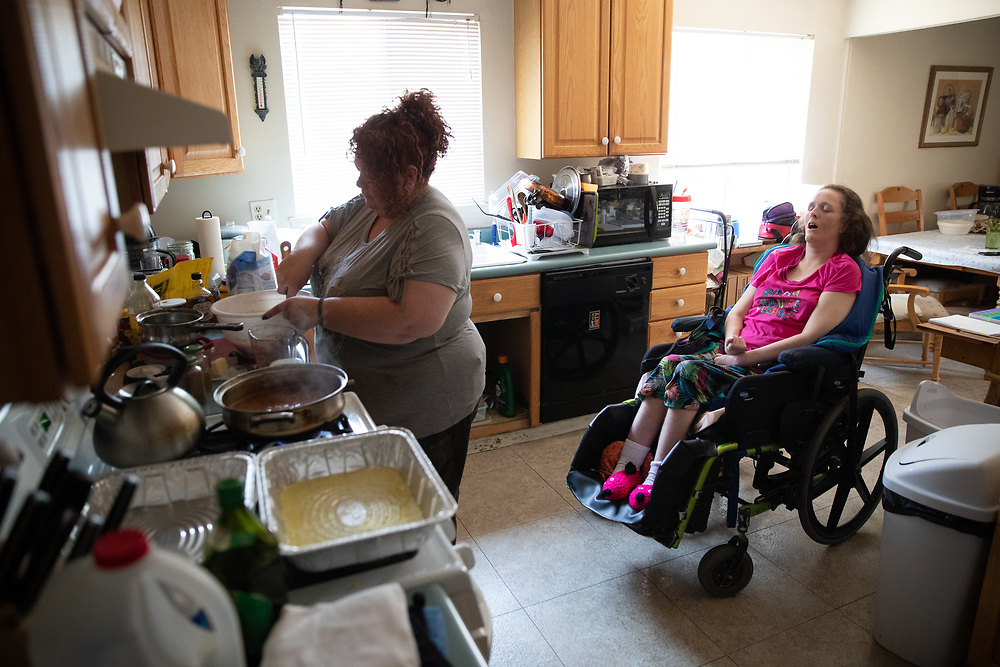 Kira Volar cares for her sister Tara, Saturday, August 4, 2018 in their home outside Sacramento, Calif. Kira is a 47-year-old fulltime caregiver to her sister, who is paralyzed and has an intellectual disability. Kira has made caregiving her life's mission after some group homes mistreated Tara.