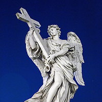 Italy, Rome, Low angle view of sculpture of an angel holding a cross on Sant Angelo Bridge at night