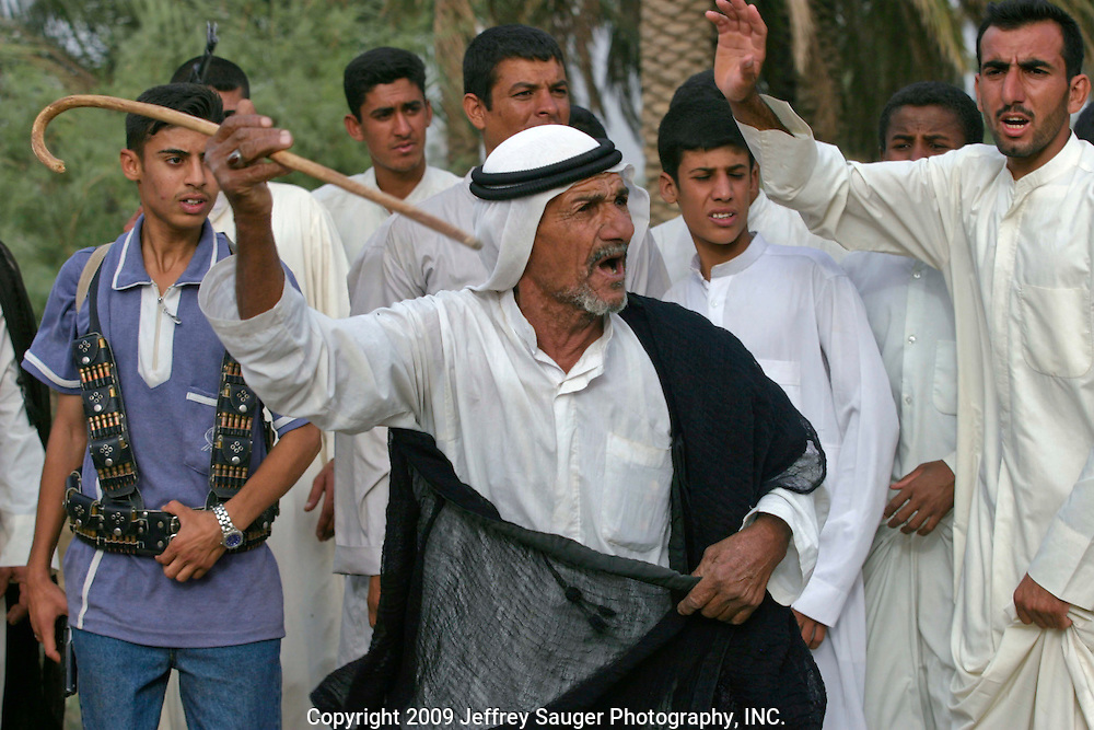 Members of Al Hacham Tribe and the extended Al-kasid family participate in Hawaies, a traditional tribal Arabic dance, at the Al-kasid family's Istikbal, or homecoming, in their home village Suq ash Shuyukh about 20 miles southeast of Nasiriyah, Iraq, Tuesday, July 29, 2003.