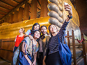 "15 OCTOBER 2014 - BANGKOK, THAILAND:  Tourists pose for a ""selfie"" in front of the Reclining Buddha in Wat Pho in Bangkok. The number of tourists arriving in Thailand in July fell 10.9 per cent from a year earlier, according to data from the Department of Tourism. The drop in arrivals is being blamed on continued uncertainty about Thailand's political situation. The tourist sector accounts for about 10 per cent of the Thai economy and suffered its biggest drop in visitors in June - the first full month after the army took power on May 22. Arrivals for the year to date are down 10.7% over the same period last year.   PHOTO BY JACK KURTZ"