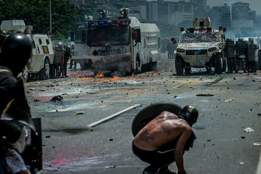 "CARACAS, VENEZUELA - MAY 10, 2017:  An anti-government protester with a message written on his back in Spanish, that says: ""Mom, today I went to defend Venezuela - if I don't return, I went with her...""  throws stones during clashes for control of the Francisco Fajardo highway with members of the National Police, who responded with a water cannon, and by heavily tear gassing and firing rubber bullets and buckshot at protesters.  The streets of Caracas and other cities across Venezuela have been filled with tens of thousands of demonstrators for nearly 100 days of massive protests, held since April 1st. Protesters are enraged at the government for becoming an increasingly repressive, authoritarian regime that has delayed elections, used armed government loyalist to threaten dissidents, called for the Constitution to be re-written to favor them, jailed and tortured protesters and members of the political opposition, and whose corruption and failed economic policy has caused the current economic crisis that has led to widespread food and medicine shortages across the country.  Independent local media report nearly 100 people have been killed during protests and protest-related riots and looting.  The government currently only officially reports 75 deaths.  Over 2,000 people have been injured, and over 3,000 protesters have been detained by authorities.  PHOTO: Meridith Kohut for The New York Times"