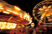 Lights and motion of amusment rides at night.