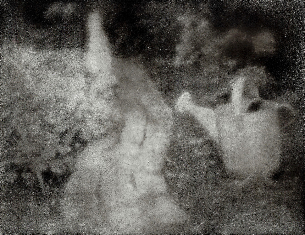 A watering can by the side of the path and a stone bunny rabbit in the distance recall memories of the story of Peter Rabbit. This image was created using the Bromoil process.