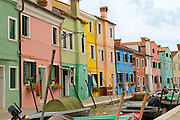 Power boats and rowboasts line a canal in Burano, an island near Venice know for its exquisite lace-making as a smartly-dressed young woman in a dress with short hair and glasses walks along the canal passing brightly colored coloured houses with geraniums and other flowers spilling out of window boxes.