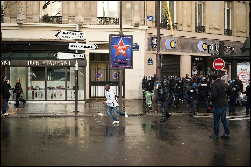 Un manifestant pro Ouattara réussit à s'échapper du cordon de CRS avant d'être rattrapé, place de la république à Paris.