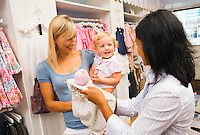 Mother with toddler girl and retail shop keeper shopping for clothes in a kids clothing boutique