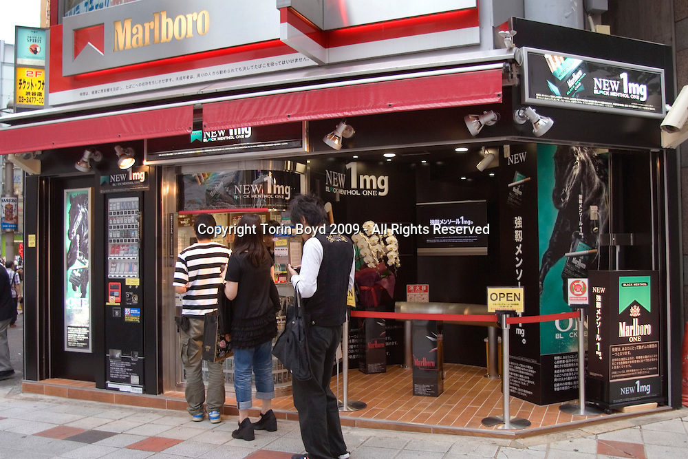 "This is a Marlboro cigarettes specialty store in Tokyo's youth mecca of Shibuya. This shop is also promoting ""Marlboro One Black Menthol"", the new brand of smokes that contains only 1 MG of nicotine. The American brand of Marlboro is distributed in Japan through Philip Morris International (PMI) which In May 2005 ended it's 32 year license agreement with Japan Tobacco Inc. to sell the Marlboro brand in Japan. Currently there are some 30 million smokers in Japan and Marlboro is one of the top selling brands. The legal smoking age in Japan is age twenty."