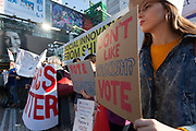"""A woman holds a sign that reads, """"Don'r Like Fascism? Vote"""" at the Vote Out the Scandal rally at Hachiko Square, Shibuya, Tokyo, Japan. Sunday November 5th 2017. Timed to coincide with President Trumps visit to Japan, About 120 Americans living in Japan and some local Japanese  protested together from 2pm to 4pm to encourage US citizens to register to vote in future elections and call on the US government to honour it responsibilities to the American people,."""