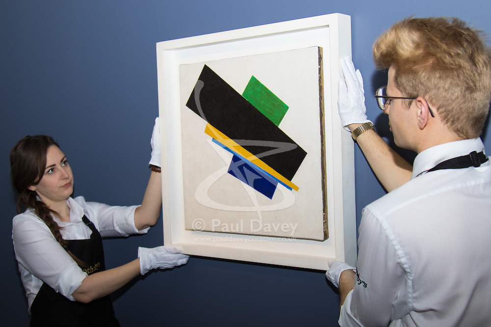 Sotheby's, London, June 19th 2015. International auctioneers Sotheby's gears up to holding what they say is London's highest valued auction of contemporary artworks, to be held on June 24th 2015 where the combined artworks are anticipated to bring in as much as £203 million. PICTURED: Sotheby's gallery technicians hang Kazimir Malevich's Suprematism, 18th Construction painted in 1915, which is expected to fetch between £20-30 million at auction. // Payment/Licencing/Contact details: Paul@pauldaveycreative.co.uk Tel: 07966016296