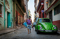 A man, carrying a large bag, walking on a street by a parked green Volkswagen Bug in Old Havana.