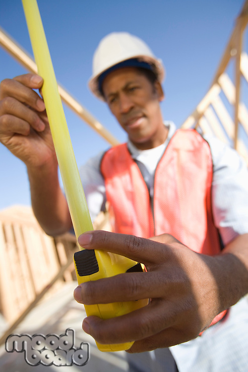 Construction worker measuring with tape measure