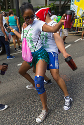 A couple trek on Ladbroke Grove as day one, Children's Day, of the Notting Hill Carnival gets underway in London. London, August 25 2019.