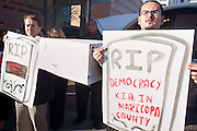 "05 DECEMBER 2009 -- PHOENIX, AZ: MANUEL DELGADO (right) and other protestors hold the coffin of ""civil rights"" during a protest in front of the Maricopa County Board of Supervisors offices in Phoenix, AZ, Monday. About 200 people from several Phoenix area civil rights groups held a mock ""funeral"" for civil rights in Phoenix Monday to protest actions taken by the Maricopa County Board of Supervisors recent decisions that limit protestors' ability to speak out against Sheriff Joe Arpiao during Board of Supervisors meetings. The protestors have been attending meetings to protest the Sheriff's series of anti-immigrant sweeps in Latino neighborhoods of Phoenix. Photo by Jack Kurtz / ZUMA Press"