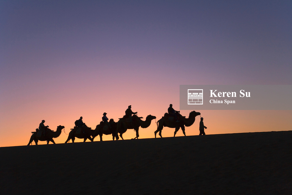 Silhouette of camel caravan with sand dune at sunrise, Dunhuang, Gansu Province, China