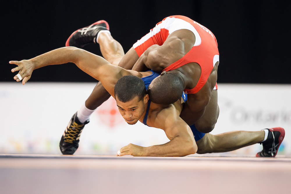 Miguel Martinez (top) of Cuba throws Wuileixis Rivas of Venezuela during their semi-final bout in the 66kg class of the men's greco-roman wrestling  at the 2015 Pan American Games in Toronto, Canada, July 15,  2015.  AFP PHOTO/GEOFF ROBINS