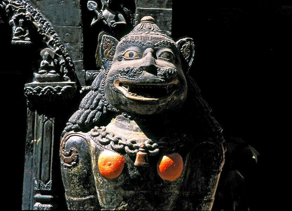 Detail of guardian lion, with orange-painted breasts, beside gate to the Golden Temple in Patan, Kathmandu, Nepal.  The face grins cheerfully