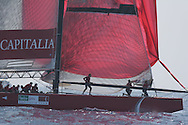 Italy's Capitalia foredeck crew hoists spinnaker and pulls down genoa jib as yacht rounds mark and sails downwind during America's Cup fleet race; Valencia, Spain.