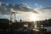 Seen from the top deck of a moving double-decker bus, driving over Waterloo Bridge, is a low sun over the capital's Southbank, the London Eye and the river Thames, on 30th January 2018, in London, England.