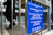 Sign showing the opening times of the City of Westminster Magistrates Court, London.