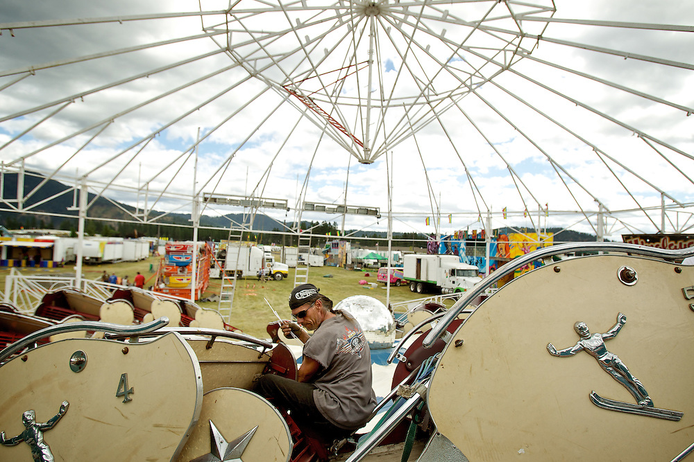 Michael Smith works on constructing the Himalaya ride on the midway Monday as the other rides and attractions are moved into position for the start of the fair.