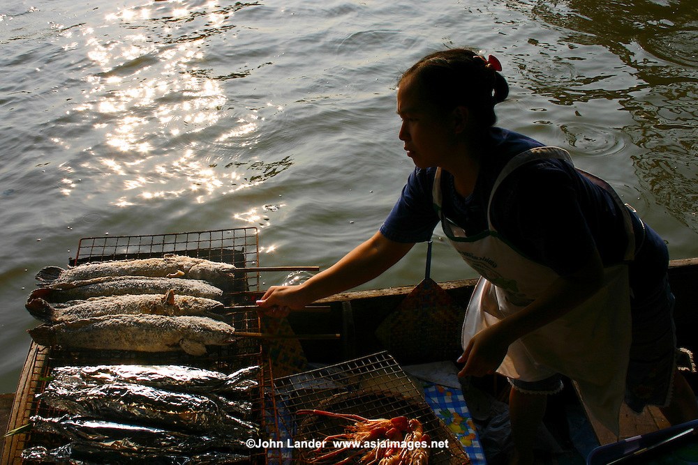 Grilling Fish at Taling Chan Floating Market, located on the canal Khlong Chak Phra and open only on weekends.  Orchard produce such as fruits, and vegetables, as well as fish are sold from boats. The idea for the floating market here was initiated in 1987 to honor King Bhumibol's 60th birthday. This is a new attraction since floating markets, an old way of life for the Thai people, had vanished from Bangkok for some time only to be revived at Taling Chan