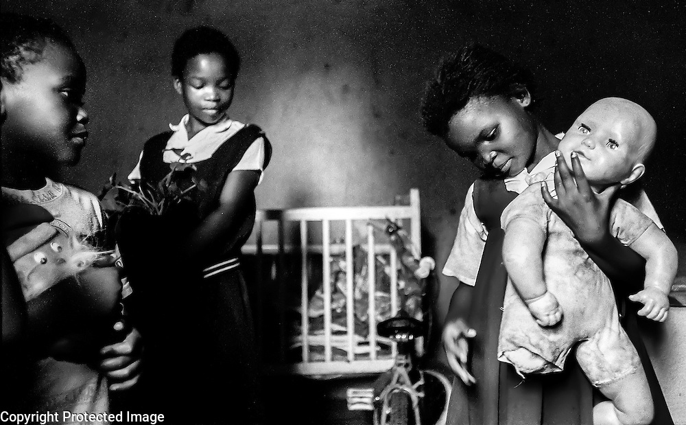 Brenda Mashila (right) examines the place where her doll's leg used to be. Left is her cousin, Michael (7), holding a Santa Claus doll and center is Brenda's cousin, Katherine (10). Mashila and her siblings and cousins live with their mother in a rural area just outside of Johannesburg.  Despite the fact that apartheid ended the year Brenda was born, her life is very much as it would have been under apartheid, with limited access to education and poor living conditions.