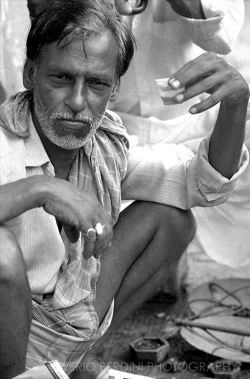 A man rests drinking a cup of chai. The indian traditional tea made with milk, spices and sugar.