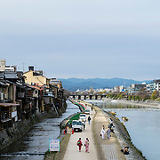 March 2016 - Kyoto, Japan : Women in kimonos walk along the Kamo River in downtown Kyoto, Japan couples sit by the water and men work on landscaping the walking path. Photos by Karsten Moran / Redux