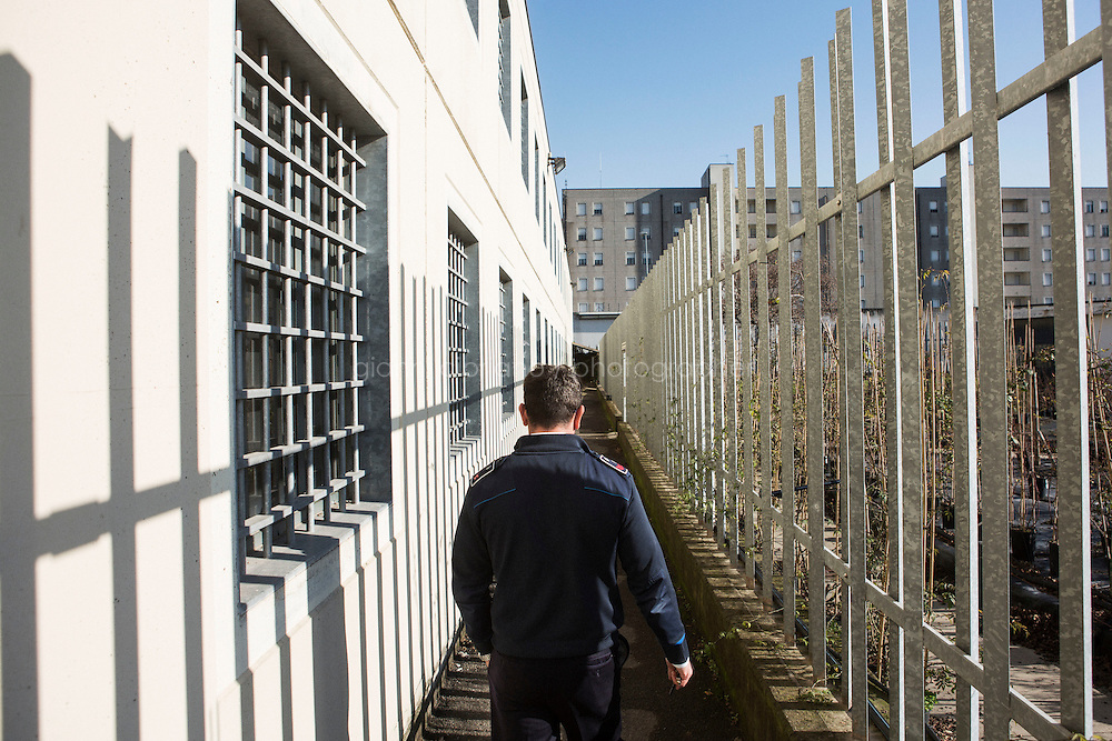 MILANO, ITALY - 1 MARCH 2016: A penitentiary guard walks in the detention area of the Bollate prison in Milan, Italy, on March 1st 2016.<br /> <br /> The Bollate prison is known for being a good example of penitentiary administration. The inmates are free to move around from one area to the other inside the prison (their cells open at 7:30am and close at 9pm) to go study, exercise in a gym, or work (in a call center, as scenographers, tailors, gardeners, cooks, typographers, among others)  in one of the 11 co-operatives inside the prison or in one of the private partnering businesses outside the prison. The turnover of the co-operatives that work inside the prison was &euro;2mln in 2012.<br /> <br /> The philosophy of the prison is to make inmates responsible. The recidivity of the Bollate prison is low (approximately 20%) compared to the national average of Italian prison, which is about 65%.<br /> <br /> In October 2015, the prison and the co-operative ABS La Sapienza inaugurated &quot;InGalera&quot; (which translates in English as &quot;InJail&quot;), the first restaurant located inside a prison and offering high-quality cooking to the public and a future to the inmates. It is open five days a week for lunch and dinner, and seats 55 people. There are 9 people involved in the project, including cooks and waiters, all regularly employed and all inmates of the prison, apart from the chef and the ma&icirc;tre d&rsquo;h&ocirc;tel, recruited from outside to guarantee the high quality of the food served. The restaurant is a project of the co-operative ABC La Sapienza - that operates inside the prison and provides more than 1,000 meals three times a day with the help of inmates they've hired - and of PwC, a multinational operating in the field of corporate consultancy. The goal of this project is to follow prisoners in rehabilitation process of social inclusion.