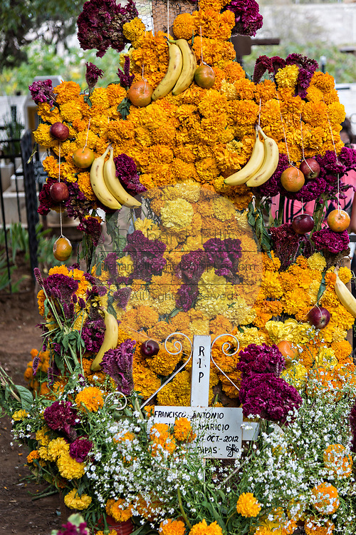 A gravesite decorated with marigolds, red cockscomb and bananas for the Day of the Dead festival October 31, 2017 in Tzintzuntzan, Michoacan, Mexico.