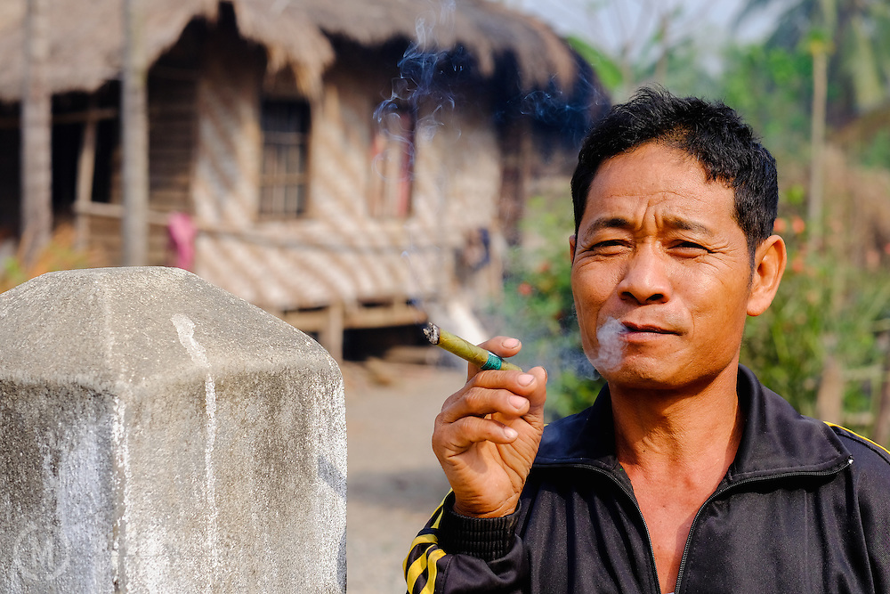 A man poses for a portrait as he smokes in a village outside of Kalaymyo, Myanmar