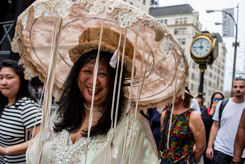 New York, NY - April 16, 2017. A woman in a large and elaborate hat bedecked in lace and with festoons of ribbons  at New York's annual Easter Bonnet Parade and Festival on Fifth Avenue.
