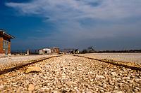 Il complesso produttivo delle saline è situato nel comune italiano di Margherita di Savoia (nome dato dagli abitanti in onore alla regina d'Italia che molto si adoperò nei confronti dei salinieri) nella provincia di Barletta-Andria-Trani in Puglia. Sono le più grandi d'Europa e le seconde nel mondo, in grado di produrre circa la metà del sale marino nazionale (500.000 di tonnellate annue).All'interno dei suoi bacini si sono insediate popolazioni di uccelli migratori e non, divenuti stanziali quali il fenicottero rosa, airone cenerino, garzetta, avocetta, cavaliere d'Italia, chiurlo, chiurlotello, fischione, volpoca..In primo piano è visibile il particolare di una linea ferroviaria per il trasporto del sale, sul sfondo costruzione e carroponte.