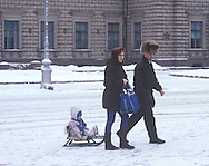 Russian parents pulling their baby on snow covered<br /> road on a sled <br /> St. Petersburg, Russia