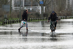 © Licensed to London News Pictures. 01/08/2014. Cyclist and pedestrian on flooded Chertsey Bridge Road. Recent bad weather has caused the river Thames in south west London and Surrey to reach very high levels. Credit : Rob Powell/LNP