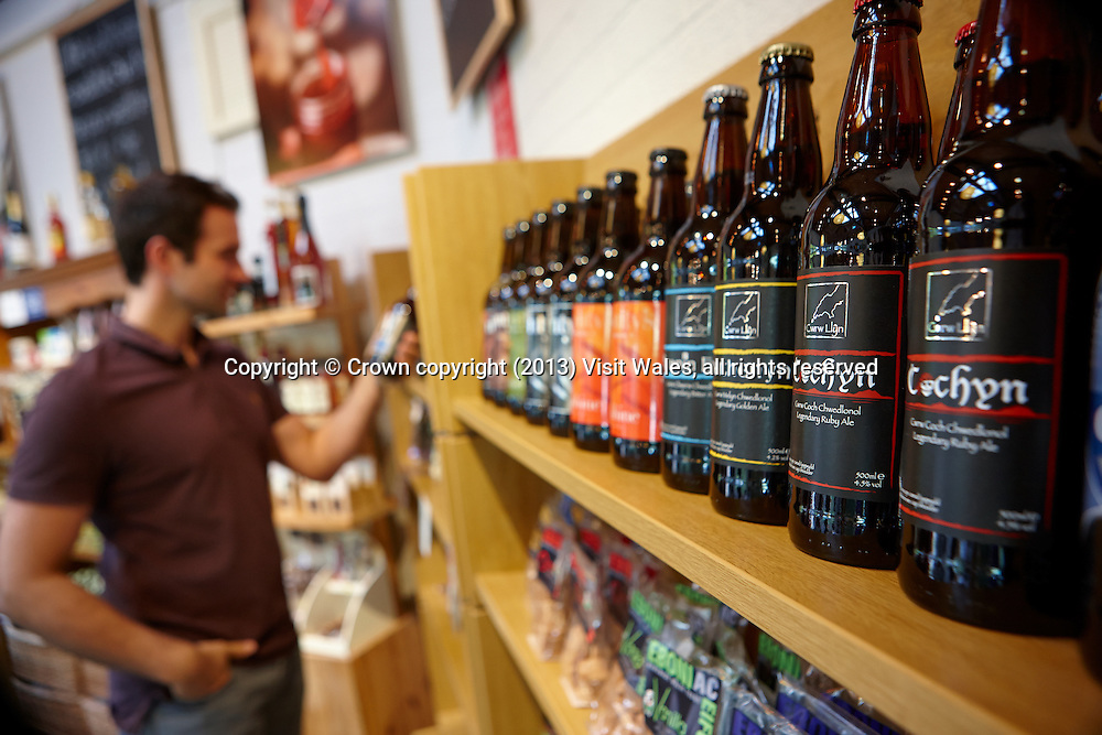 Man looking at bottles of beer at Bwtri Y Crochan food shop<br /> Corris Craft Centre<br /> Corris<br /> Gwynedd<br /> Mid<br /> Tourist Attractions