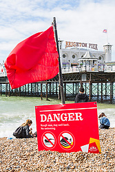 © Licensed to London News Pictures. 19/08/2017. Brighton, UK. Red flag's and warning signs have been placed on the beach of Brighton and Hove as powerful waves are hitting the seaside resort. Photo credit: Hugo Michiels/LNP